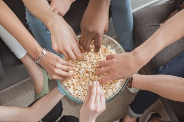 top view of female and male hands taking popcorn from bowl