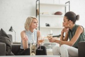 Fotografie multiethnic young women sitting and talking with glasses of white wine