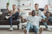 junge fröhliche multikulturelle Männerfreunde schauen Fußballspiel und feiern mit Bierflaschen in der Hand