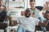 Gruppe von multikulturellen junge Männer beobachten Fußballspiel und feiert mit Flaschen Bier