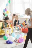 due giovani donne che tengono stringa con ghirlande di partito e i loro amici maschi decorare la stanza dietro