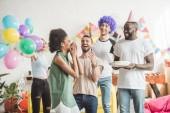 Spokojení mladí muži a ženy slaví s narozeninovým dortem na překvápko