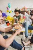 Párty rozdílní lidé jíst narozeninový dort a držení nápoje