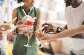 Mladí muži a ženy, přípitky šampaňským na narozeninovou oslavu