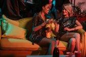 Fotografie Mladí mnohonárodnostní ženy slaví s nápoje v útulném pokoji