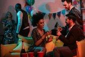 Muži a ženy slaví s nápoji na domácí párty