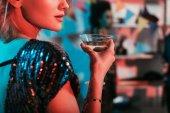Blond žena držící sklo s koktejl party