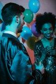 Mann und Frau Gläser halten und sprechen auf party