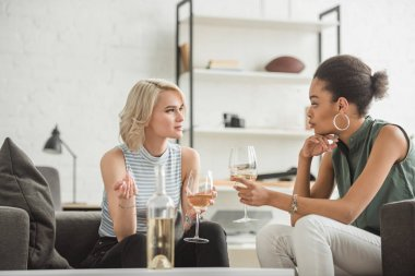 multiethnic young women sitting and talking with glasses of white wine