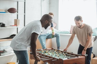 two young multiethnic friends playing table football