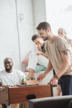 smiling man playing table football while friends watching