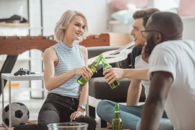 african american man sitting near smiling young woman clinking bottles of beer with friend