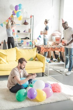 group of multicultural friends decorating room with party garlands and balloons