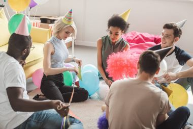 group of young multicultural friends in party hats sitting on floor with balloons in decorated room