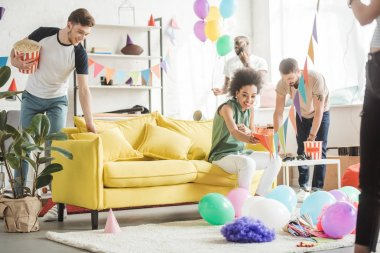 multicultural young friends decorating living room with balloons and party garlands