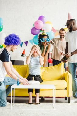 Happy friends greeting young woman with birthday cake on surprise party