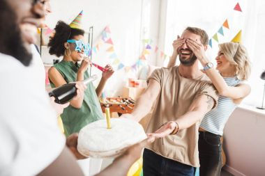 Smiling young people covering eyes of young friend and greeting him with birthday cake