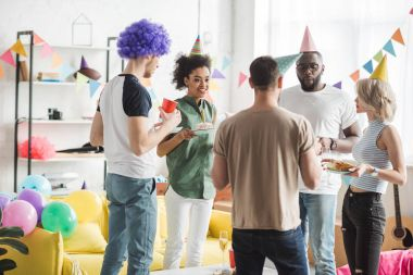 Multiracial friends celebrating birthday with drinks in decorated room