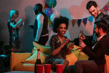 Multiracial friends having party with drinks in decorated room