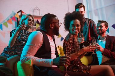 Young multiracial people celebrating with drinks in cozy room