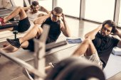 hezký sportovní přátel dělá sit ups společně v tělocvičně