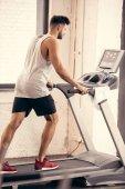 Seitenansicht des schönen Sportler gehen auf Laufband im Fitnessstudio
