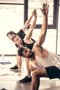 handsome sportsmen simultaneously exercising and stretching in gym