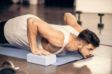 handsome sportsman doing plank on yoga blocks and yoga mat in gym