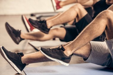 cropped image of sportsmen doing sit ups together in gym