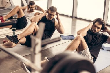 handsome sportive friends doing sit ups together in gym