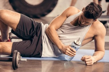 tired sportsman lying on floor in gym and holding bottle of water