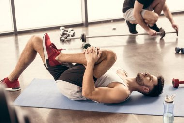 handsome sportsmen stretching legs on yoga mat in gym