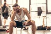 Fotografie lächelnd Sportler sitzen mit Flasche Wasser bei Bankdrücken im Fitness-Studio