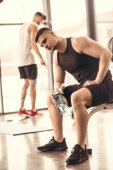 Fotografie hezký sportovci odpočívá a drží láhev vody v tělocvičně