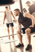 Photo side view of handsome sportsmen resting and holding bottle of water in gym