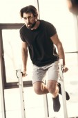 Photo full length view if athletic young man in sportswear exercising on bars in gym