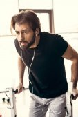Photo muscular young man in earphones exercising on bars and looking away in gym