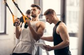 trainer using digital tablet and helping muscular sportsman exercising with fitness straps in gym
