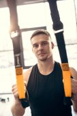 handsome young man training with fitness straps and looking at camera in gym