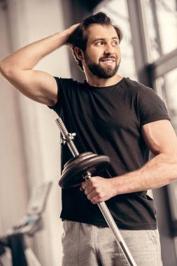 smiling sportsman holding iron bar and touching hair in gym