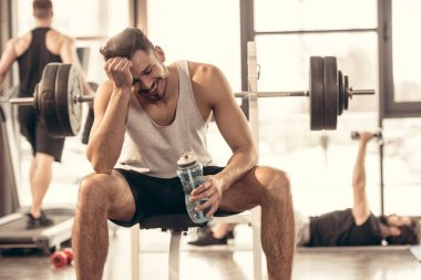 smiling sportsman sitting with bottle of water on bench press in gym