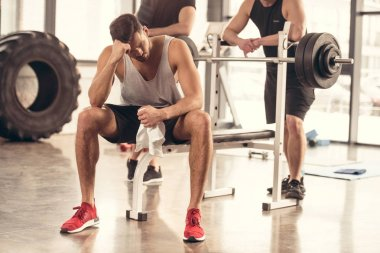 handsome tired sportsman sitting and resting on bench press in gym
