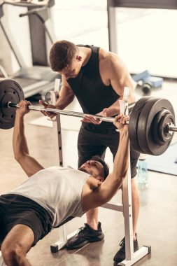 muscular trainer helping sportsman lifting barbell with heavy weights in gym