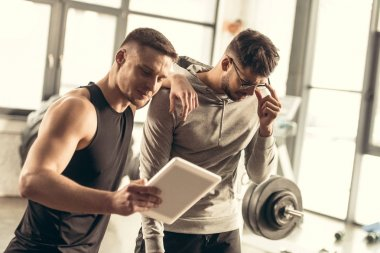 handsome trainer showing results of exercising on tablet to tired sportsman in gym