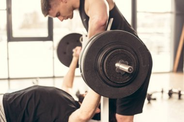 handsome trainer helping sportsman lifting barbell with heavy weights in gym