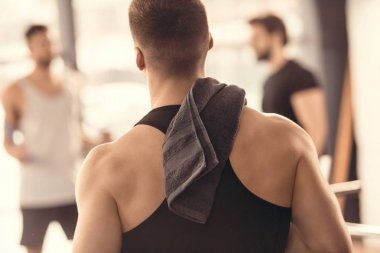 back view of muscular sportsman with towel on shoulder