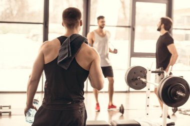 back view of muscular sportsman looking at friends in gym