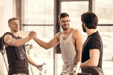 handsome smiling sportsmen greeting in gym