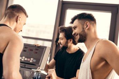 handsome sportsmen setting treadmill in gym