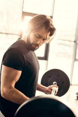 handsome sportsman training with barbell in gym